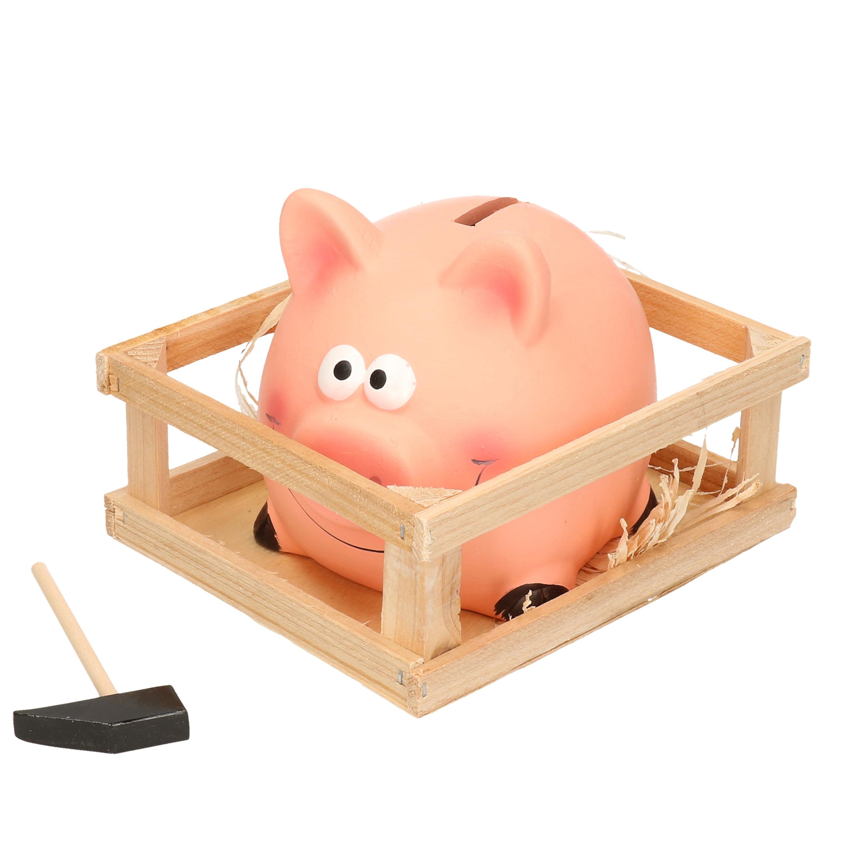 Roze spaarvarken met hamer in kistje